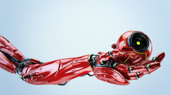Red robotic arm holding remote camera drone
